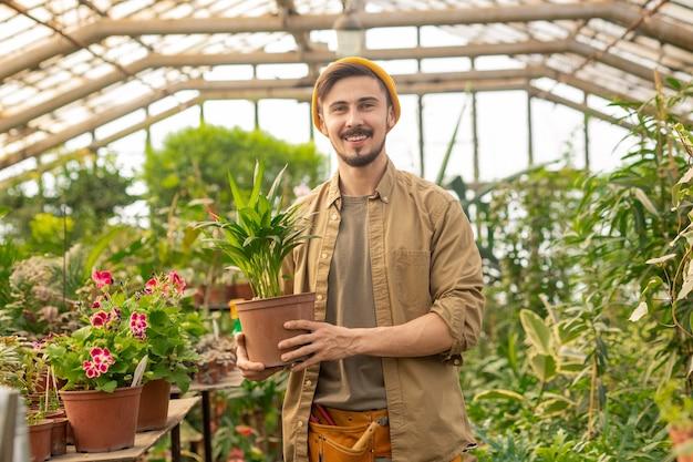 Portret szczęśliwy przystojny facet w czapce hipster trzymając roślinę doniczkową przy wyborze rośliny w przedszkolu
