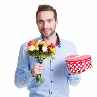 Portret szczęśliwy przystojny mężczyzna z kwiatami i prezentem - na białym tle.