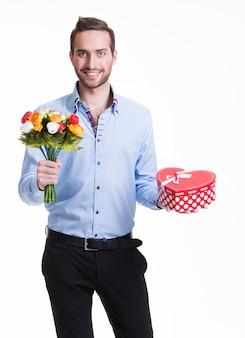 Portret szczęśliwy przystojny mężczyzna z kwiatami i prezentem - na białym tle