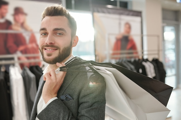 Portret szczęśliwy przystojny młody biznesmen niosąc torby na zakupy na ramieniu podczas robienia zakupów w centrum handlowym