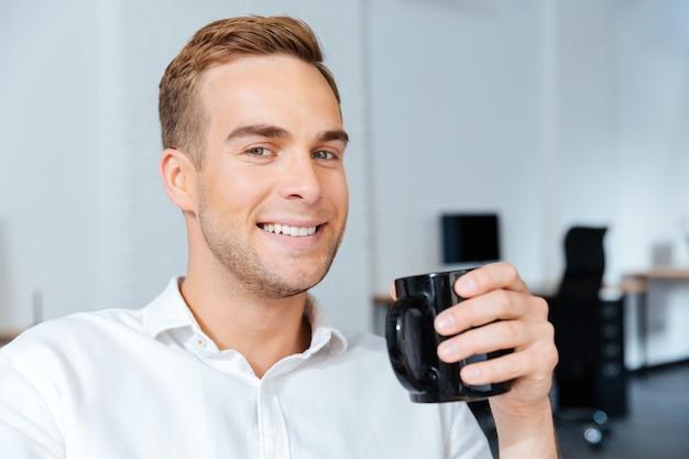 Portret szczęśliwy przystojny młody biznesmen pije kawę w biurze