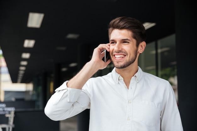 Portret szczęśliwy przystojny młody biznesmen rozmawia przez telefon komórkowy w pobliżu centrum biznesowego