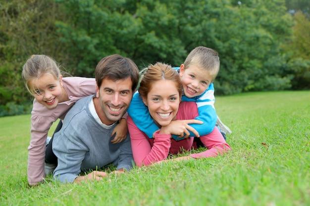 Portret szczęśliwy rodzinny łgarski puszek w trawie