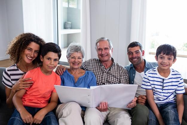 Portret szczęśliwy rodzinny obsiadanie na kanapie i patrzeć album fotograficznego