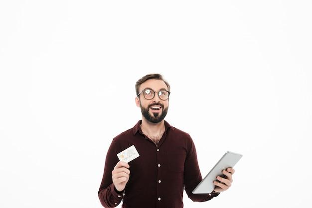 Portret szczęśliwy rozochocony mężczyzna mienia pastylki komputer