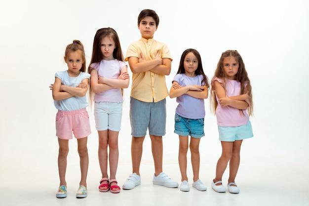 Portret szczęśliwy słodkie małe dzieci chłopca i dziewczynki w stylowych ubrań, patrząc na kamery na białej ścianie