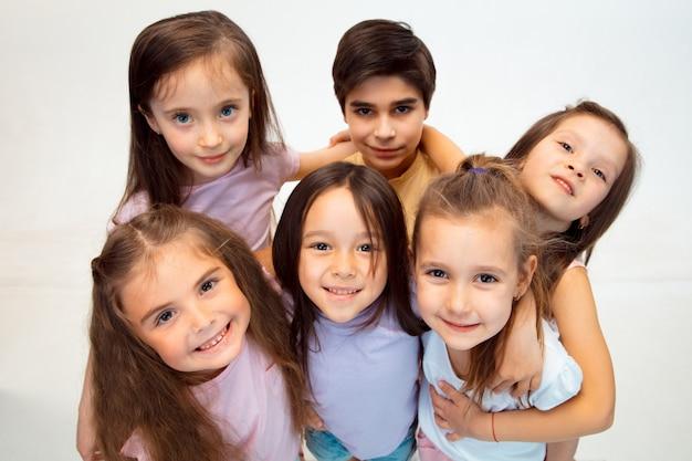 Portret szczęśliwy słodkie małe dzieci chłopca i dziewczynki w stylowych ubrań, patrząc z przodu na białej ścianie studia