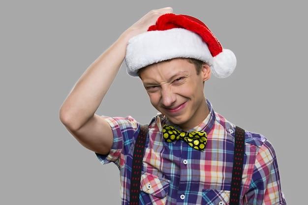 Portret szczęśliwy śmieszny chłopiec w kapeluszu santa. bliska nastoletni facet w kapeluszu boże narodzenie pozowanie na szarym tle. wesołych świąt i szczęśliwego nowego roku.