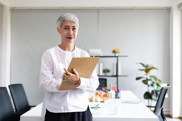 Portret szczęśliwy starszy bizneswoman z okularami patrząc na kamery. 60s siwowłosa kobieta lidera wykonawczego.