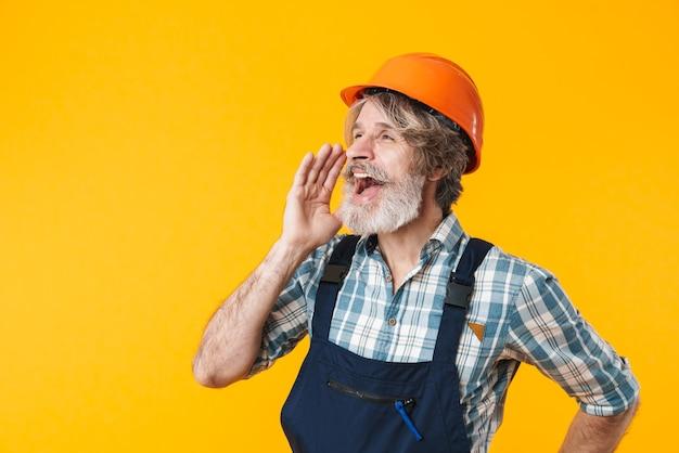 Portret szczęśliwy starszy siwowłosy brodaty mężczyzna budowniczy w hełmie pozuje na białym tle nad żółtą ścianą krzyczy na bok.