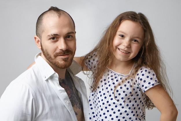 Portret szczęśliwy stylowy nowoczesny młody ojciec z brodą i twórczą fryzurą pozowanie w studio
