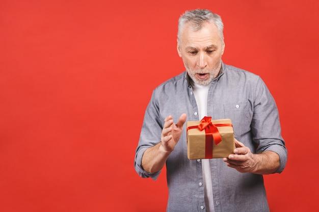 Portret, szczęśliwy super podekscytowany starszy mężczyzna, otwarte, nieopakowane pudełka na prezenty, odizolowane na czerwonym tle, ciesząc się prezentem.