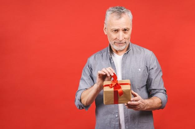 Portret, szczęśliwy super podekscytowany starszy mężczyzna, otwarte, nieopakowane pudełka na prezenty, odizolowane na czerwonym tle