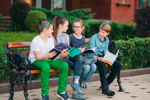 Portret szczęśliwy szkolnych kolegów. koledzy siedzą z książkami w drewnianej ławce w parku miejskim i studiują w słoneczny dzień.