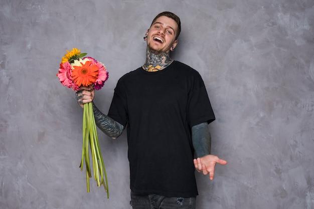 Portret szczęśliwy tatuujący młody człowiek trzyma gerbera kwiaty w ręce wzrusza ramionami przeciw popielatemu tłu