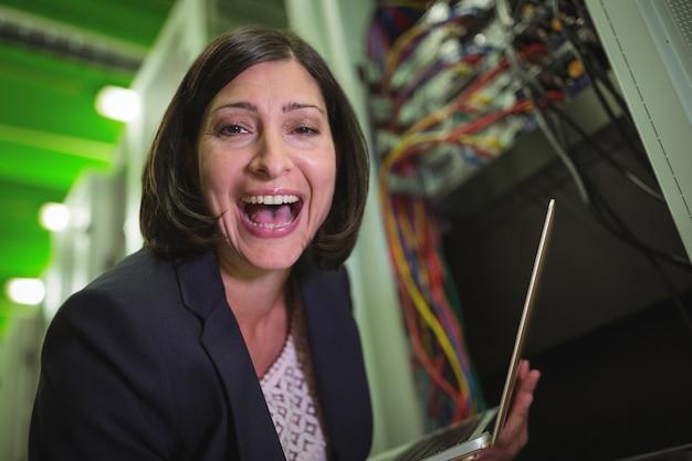 Portret szczęśliwy technika mienia laptop