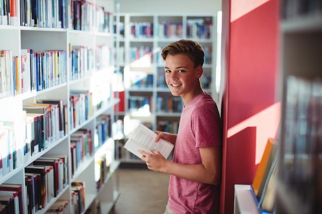 Portret szczęśliwy uczeń czytanie książki w bibliotece