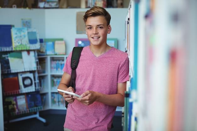 Portret szczęśliwy uczeń trzymając cyfrowy tablet w bibliotece