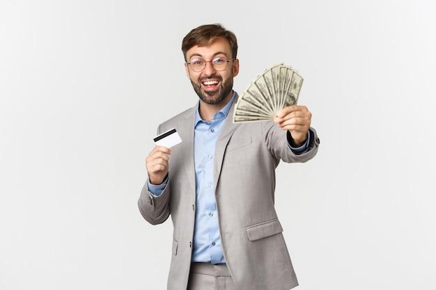 Portret szczęśliwy udany biznesmen posiadający kartę kredytową, pokazując pieniądze