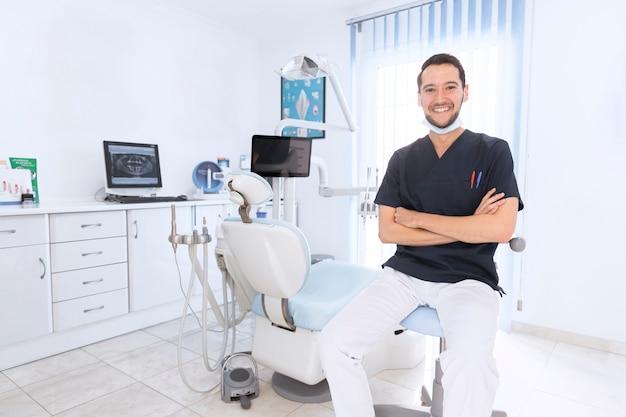 Portret szczęśliwy ufny dentysta w klinice