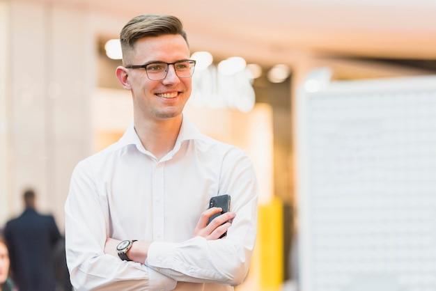 Portret szczęśliwy ufny młody biznesmen z ręką krzyżował mienie telefon komórkowego w ręce
