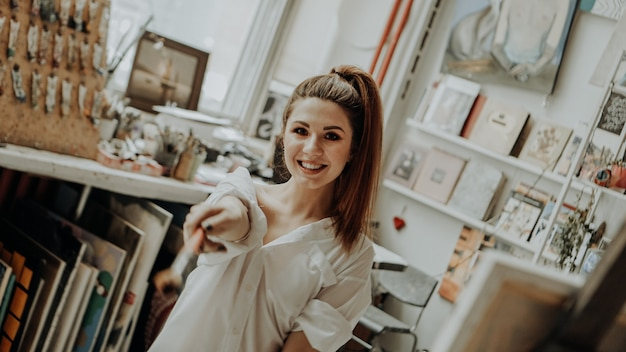 Portret szczęśliwy uśmiechający się artystki z pędzlem w warsztacie artystycznym. selektywne skupienie. zdjęcie w stylu vintage
