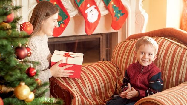 Portret szczęśliwy uśmiechający się mały chłopiec siedzi w fotelu i czeka na matkę, dając mu świąteczny prezent. idealny obraz na ferie zimowe i uroczystości