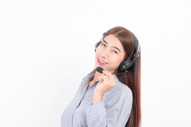 Portret szczęśliwy uśmiechający się operator telefoniczny obsługi klienta kobiece krótkie włosy, ubrany w białą koszulę z zestawem słuchawkowym stojący z jednej strony trzymający słuchawkę na białym tle.