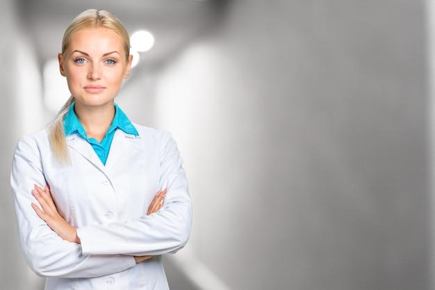 Portret szczęśliwy uśmiechający się pewny siebie zadowolony piękny z blond włosami kobiet lekarza rodzinnego na sobie biały płaszcz