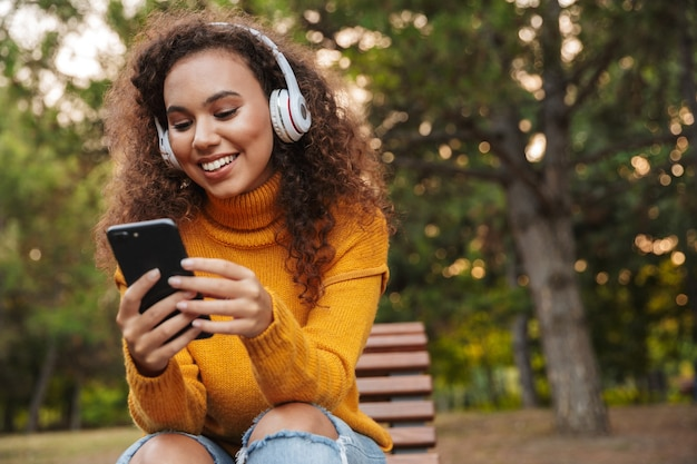 Portret szczęśliwy uśmiechający się piękna młoda kędzierzawa kobieta siedzi na ławce w parku na zewnątrz, słuchając muzyki w słuchawkach przy użyciu telefonu komórkowego.