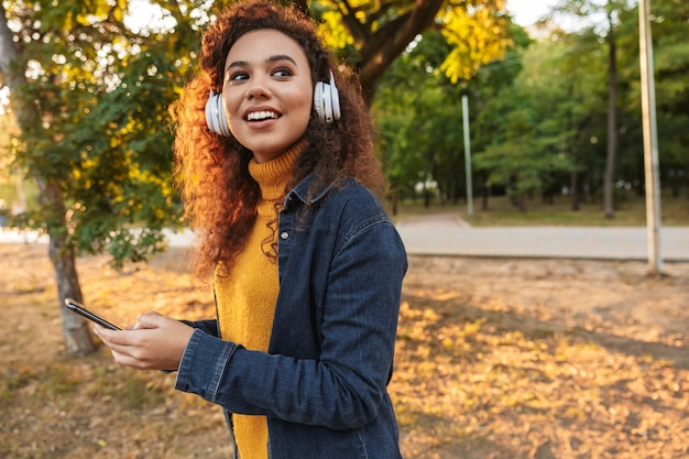 Portret szczęśliwy uśmiechający się piękne młode kręcone kobiety spaceru w parku na zewnątrz słuchania muzyki w słuchawkach przy użyciu telefonu komórkowego.