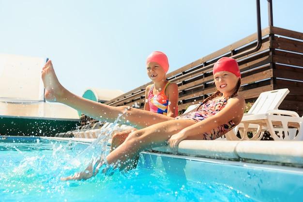 Portret szczęśliwy uśmiechający się piękne nastolatki na basenie
