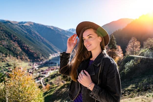 Portret szczęśliwy uśmiechnięty atrakcyjny kobieta podróżnik w filcowym kapeluszu i czarnej dżinsowej kurtce stoi na górach podczas podróży po turcji
