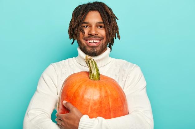 Portret szczęśliwy uśmiechnięty facet ma szczęśliwy nastrój, nosi dużą pomarańczową dynię, nosi biały sweter, odizolowany na niebieskim tle.