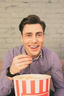 Portret szczęśliwy uśmiechnięty mężczyzna jedzenie popcornu w domu