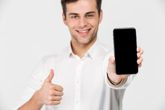 Portret szczęśliwy uśmiechnięty mężczyzna pokazuje pustego ekran