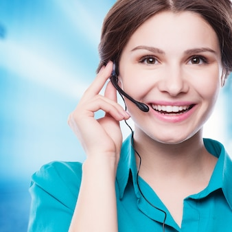 Portret szczęśliwy uśmiechnięty rozochocony młody poparcie telefonu operator w słuchawki pokazuje copyspace teren lub coś