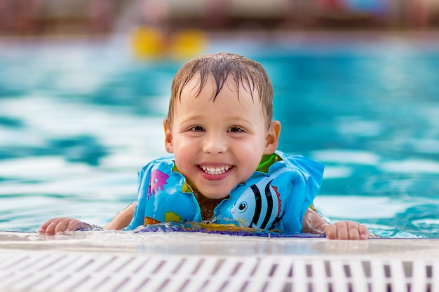 Portret szczęśliwy wesoły chłopca w niebieskiej kamizelce ratunkowej w basenie w pobliżu hotelu. bezpieczeństwo dziecka w wodzie.