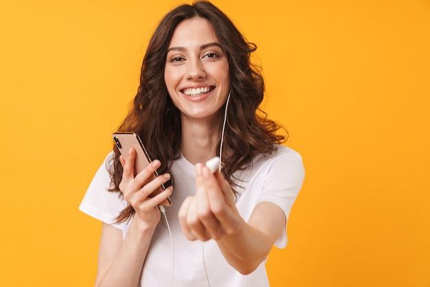 Portret szczęśliwy wesoły młoda kobieta pozowanie na białym tle nad żółtą ścianą słuchania muzyki za pomocą telefonu komórkowego daje jedną słuchawkę.