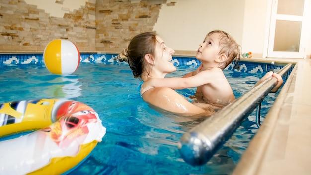Portret szczęśliwy wesoły młody mothet z 3-letnim chłopcem malucha grając w basenie w domu. dziecko uczy się pływania z rodzicem. rodzina bawi się latem