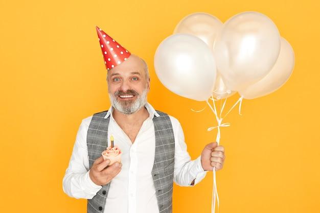 Portret szczęśliwy wesoły starszy brodaty mężczyzna ubrany w eleganckie ubrania i kapelusz stożka pozowanie na białym tle trzymając urodzinową babeczkę i balony z helem