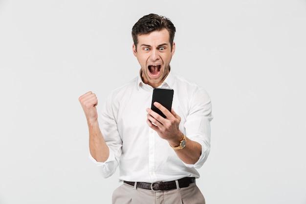 Portret szczęśliwy zadowolony mężczyzna patrzeje telefon komórkowego