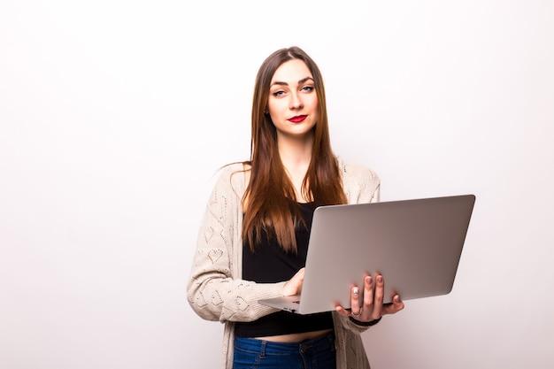 Portret szczęśliwy zaskoczony kobiety stojącej z laptopem na szaro