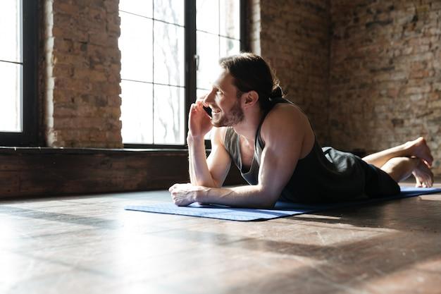 Portret szczęśliwy zdrowy sportowiec opowiada na telefonie komórkowym