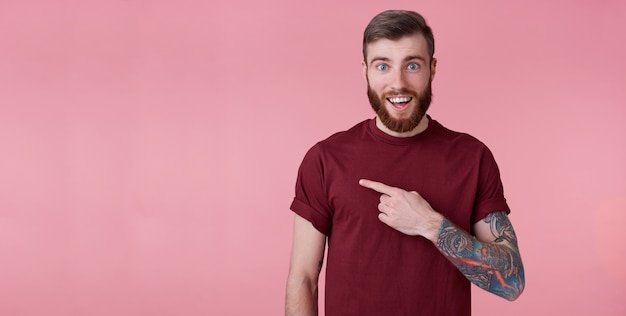 Portret szczęśliwy zdumiony młody przystojny brodaty mężczyzna w czerwonej koszuli, chce zwrócić twoją uwagę w lewo w miejsce kopii, wskazując palcami i patrzeć na niego, stoi na różowym tle.