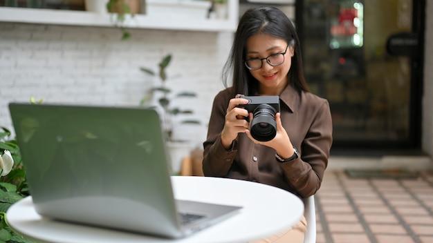 Portret szczęśliwy żeński fotograf uśmiecha się i sprawdza zdjęcie w aparacie cyfrowym