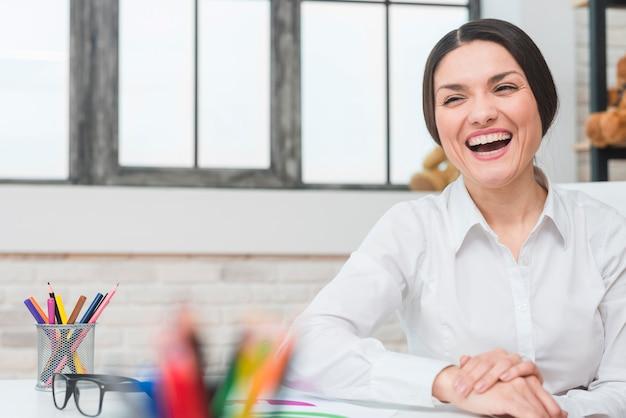 Portret szczęśliwy żeński psycholog śmia się w biurze