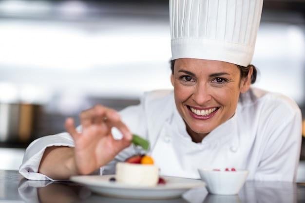 Portret szczęśliwy żeński szefa kuchni garnirowanie na jedzeniu