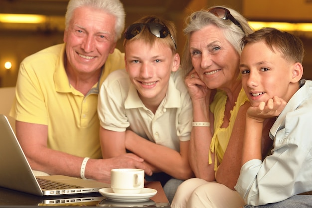 Portret szczęśliwych chłopców z dziadkami i laptopem