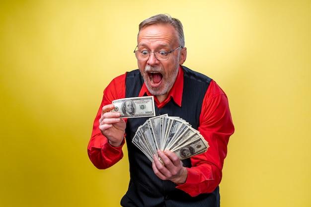 Portret szczęśliwych i białych zębów uśmiech starszy stary biznesmen. mężczyzna trzyma pieniądze w rękach. ubrana w czerwoną koszulę, na białym tle na żółtym tle. ludzkie emocje i mimika twarzy